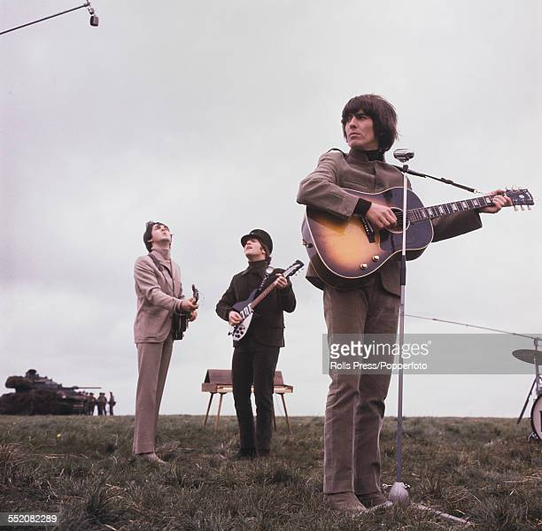 Paul McCartney John Lennon and George Harrison of The Beatles pictured playing their guitars on Salisbury Plain Wiltshire during filming for their...