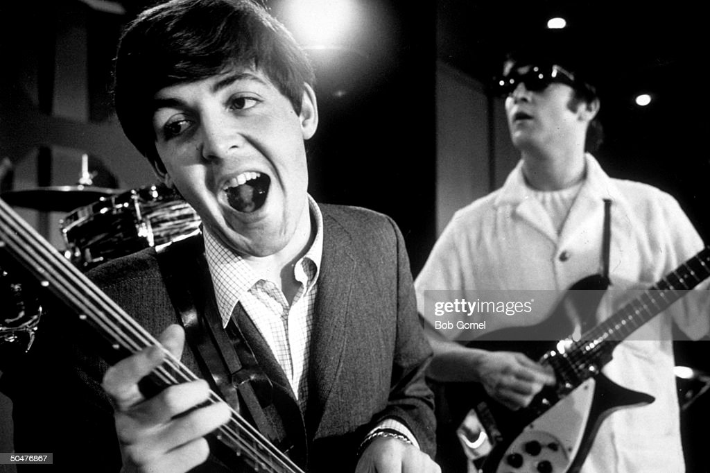 Paul McCartney & John Lennon of rock group the Beatles rehearsing on stage during American tour.