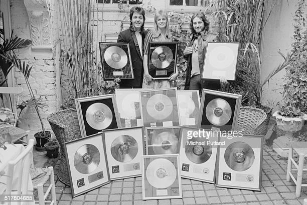 Paul McCartney Linda McCartney and Denny Laine of British rock group Wings with gold discs awarded for their album 'Band On The Run' 2nd May 1974