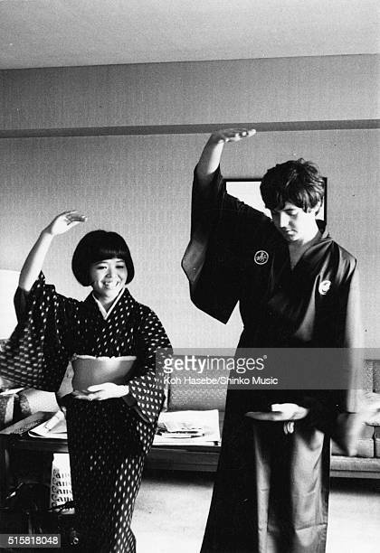 Paul McCartney of the Beatles wearing a kimono and posing with journalist Rumi Hoshika during an interview for Japanese music magazine 'Music Life'...