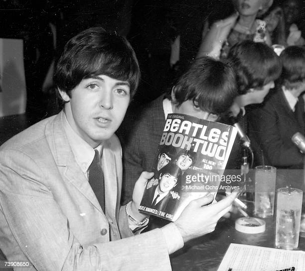 Paul McCartney of the rock and roll band 'The Beatles' poses for a portrait holding a fanzine entitled 'The Beatles Book Two' backstage at their...