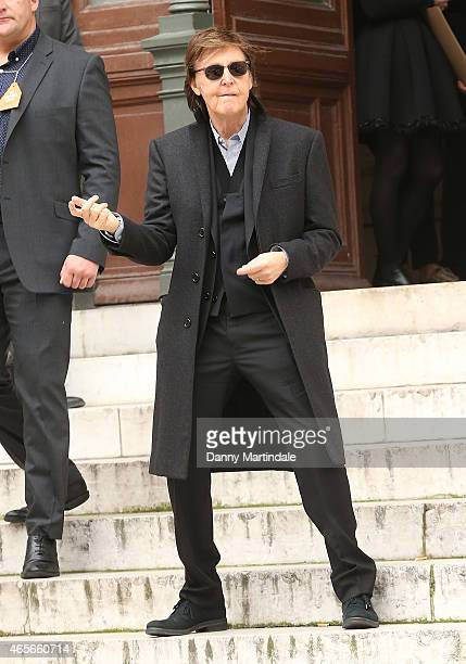 Paul McCartney plays air guitar as he leaves the Stella McCartney show at the Opera Garnier during Paris Fashion Week Fall Winter 2015/2016 on March...