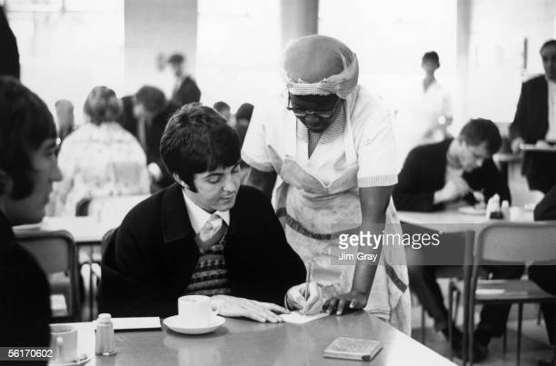 Paul McCartney signs an autograph for a fan whilst taking refreshment in a London Transport workers' canteen in Allsop Place London 1967 He is...