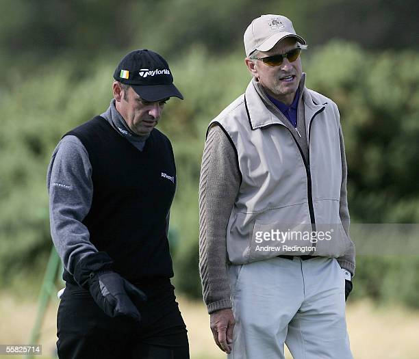 Paul McGinley of Ireland and actor Michael Douglas talk on the 14th hole fairway during the first round of the Dunhill Links Championships at the...