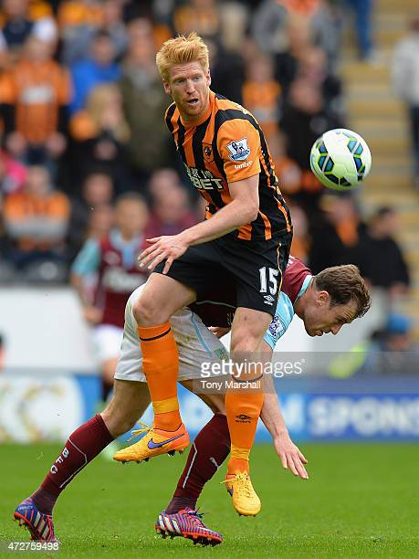 Paul McShane of Hull City is tackled by Ashley Barnes of Burnley during the Barclays Premier League match between Hull City and Burnley at KC Stadium...