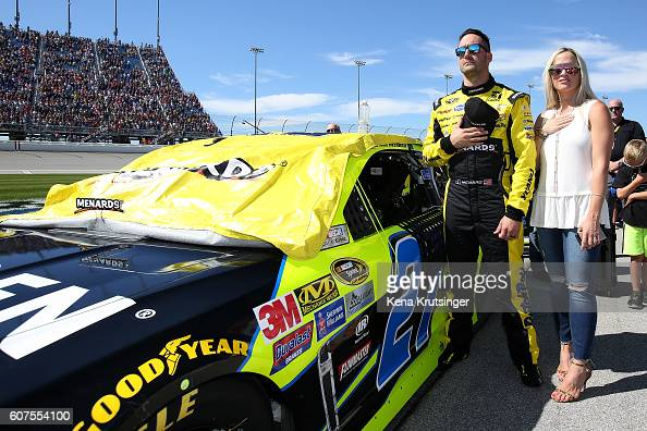 Paul Menard driver of the Moen/Menards Chevrolet stands for the national anthem with his wife Jennifer during the NASCAR Sprint Cup Series Teenage...