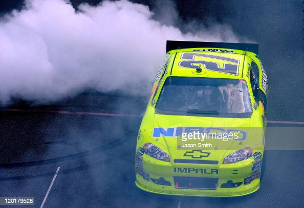 Paul Menard driver of the NIBCO/Menards Chevrolet celebrates with a burnout after winning the NASCAR Sprint Cup Series Brickyard 400 at Indianapolis...