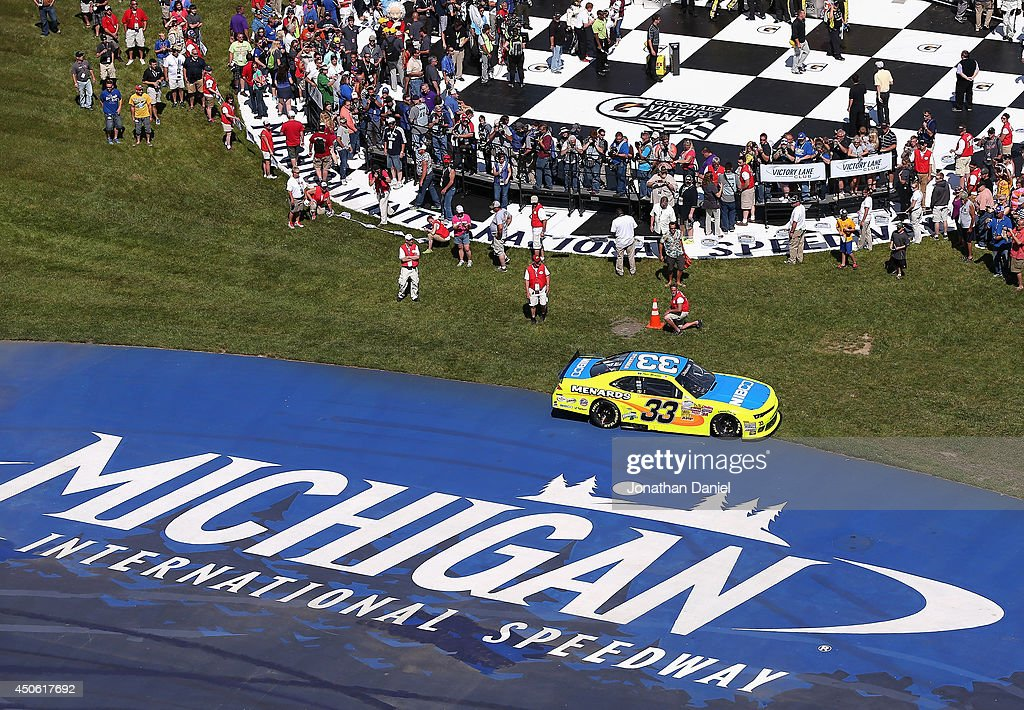 Paul Menard, driver of the #33 Nibco/Menards Chevrolet, drives through the grass after winning the NASCAR Nationwide Series Ollie's Bargain Outlet 250 at Michigan International Speedway on June 14, 2014 in Brooklyn, Michigan.