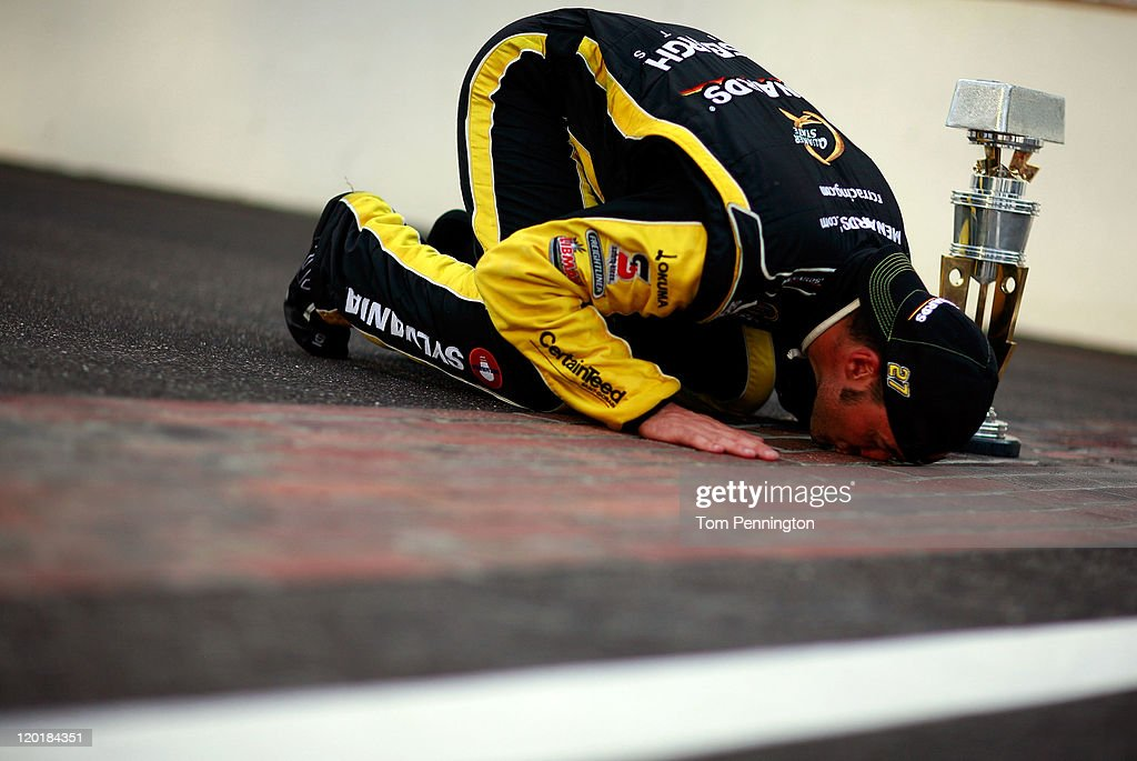 Paul Menard driver of the NIBCO/Menards Chevrolet poses as he kisses the bricks after winning the NASCAR Sprint Cup Series Brickyard 400 at...