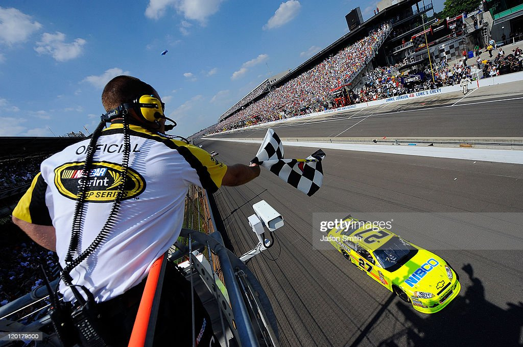Paul Menard driver of the NIBCO/Menards Chevrolet takes the checkered flag as he crosses the finish line to win the NASCAR Sprint Cup Series...
