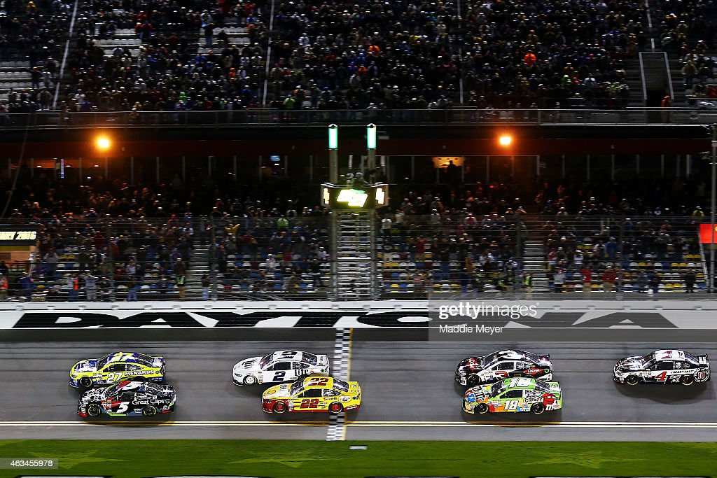 Paul Menard driver of the Peak/Menard's Chevrolet and Kasey Kahne driver of the Great Clips Chevrolet lead the field through the green flag to start...
