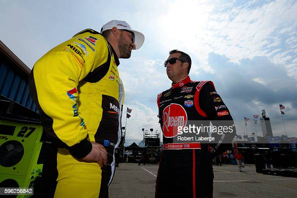 Paul Menard driver of the SYLVANIA/Menards Chevrolet talks to Sam Hornish Jr driver of the Thrivent Financial Chevrolet during practice for the...