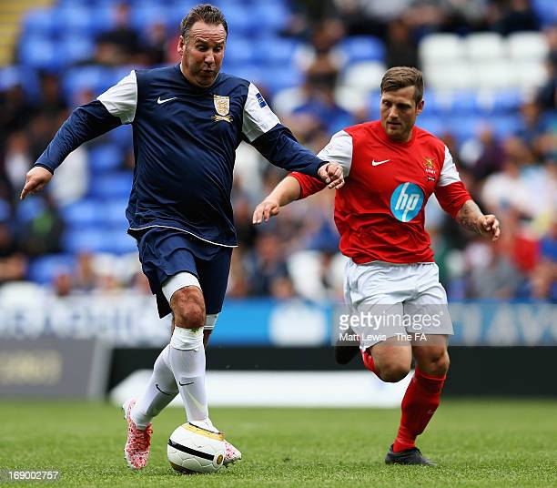Paul Merson is tackled by Jay Bates of the Army FA during the Army FA and FA Legends Match at Madejski Stadium on May 18 2013 in Reading England