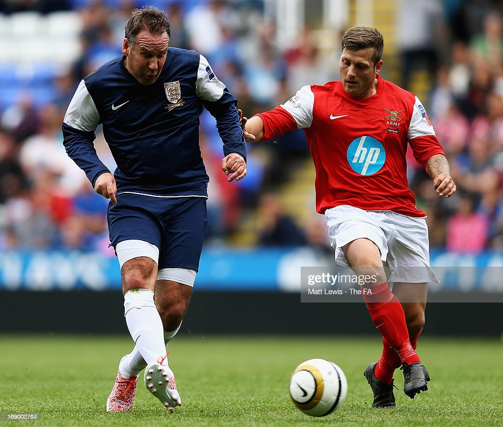<a gi-track='captionPersonalityLinkClicked' href=/galleries/search?phrase=Paul+Merson&family=editorial&specificpeople=243283 ng-click='$event.stopPropagation()'>Paul Merson</a> is tackled by Jay Bates of the Army FA during the Army FA and FA Legends Match at Madejski Stadium on May 18, 2013 in Reading, England.