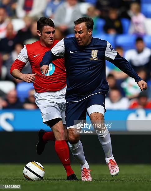 Paul Merson of the FA Legends and Gavin Greenfield of the Army FA challenge for the ball during the Army FA and FA Legends Match at Madejski Stadium...