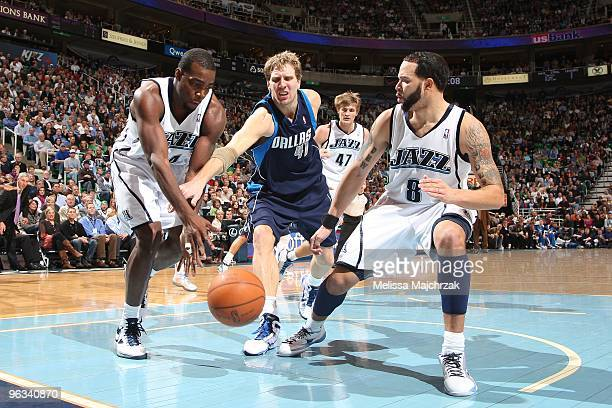 Paul Millsap and Deron Williams of the Utah Jazz battles for the loose ball with Dirk Nowitzki of the Dallas Mavericks at EnergySolutions Arena on...