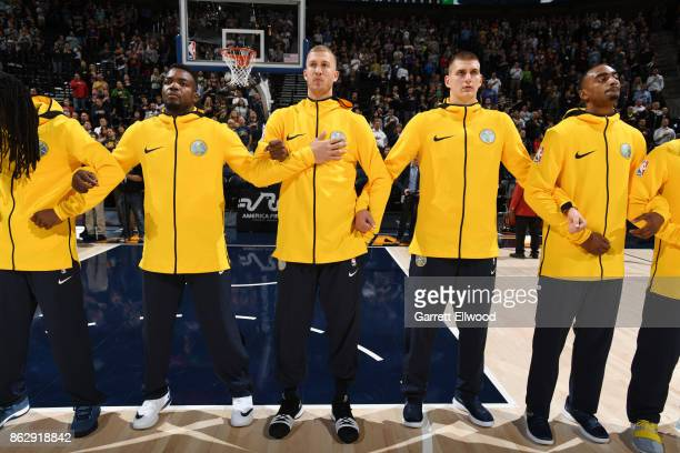 Paul Millsap and Nikola Jokic of the Denver Nuggets with their teammates stand for the National Anthem before the game against the Utah Jazz on...