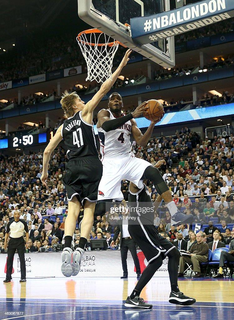 Paul Millsap of Atlanta Hawks battles with Andrei Kirilenko of Brooklyn Nets during the Eastern Conference NBA match between Brooklyn Nets and Atlanta Hawks at O2 Arena on January 16, 2014 in London, England.