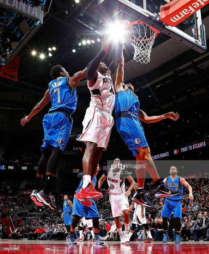 Paul Millsap of the Atlanta Hawks attacks the basket between AlFarouq Aminu and Richard Jefferson of the Dallas Mavericks at Philips Arena on...