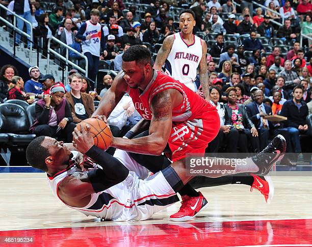 Paul Millsap of the Atlanta Hawks battles for a loose ball against Terrence Jones of the Houston Rockets on March 3 2015 at Philips Arena in Atlanta...