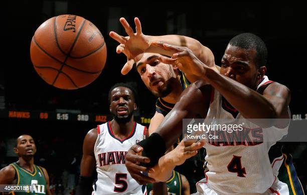 Paul Millsap of the Atlanta Hawks battles for a rebound against Enes Kanter of the Utah Jazz at Philips Arena on December 20 2013 in Atlanta Georgia...