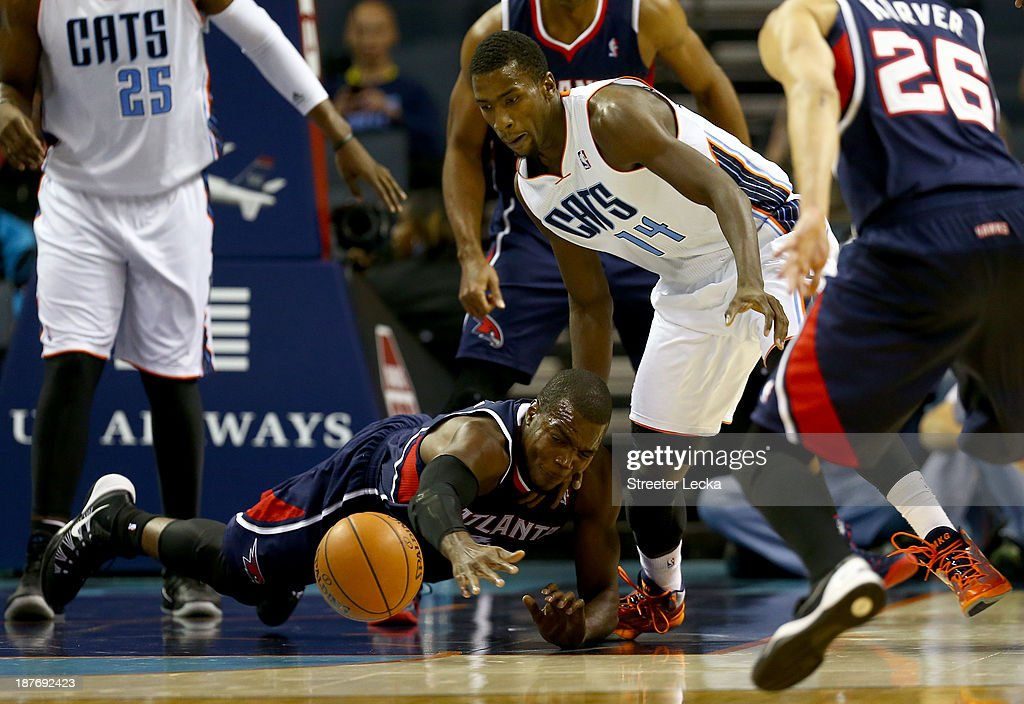 Paul Millsap #4 of the Atlanta Hawks dives after a loose ball with Michael Kidd-Gilchrist #14 of the Charlotte Bobcats during their game at Time Warner Cable Arena on November 11, 2013 in Charlotte, North Carolina.