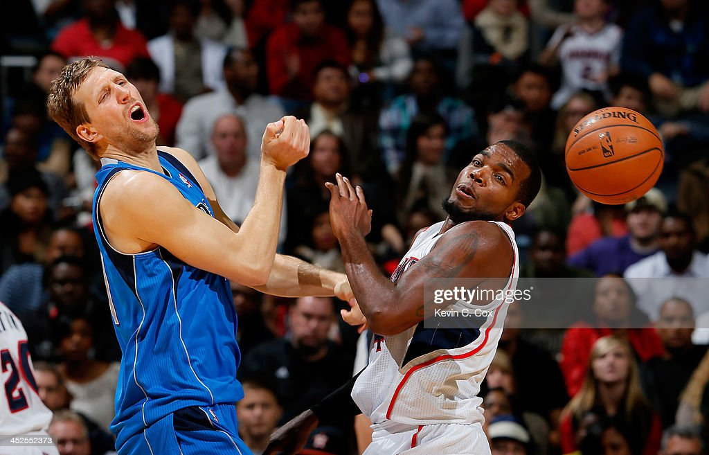 Paul Millsap #4 of the Atlanta Hawks fouls Dirk Nowitzki #41 of the Dallas Mavericks at Philips Arena on November 29, 2013 in Atlanta, Georgia.