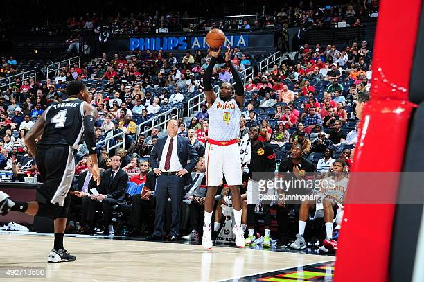 Paul Millsap of the Atlanta Hawks shoots against Deshaun Thomas of the San Antonio Spurs on October 14 2015 at Philips Arena in Atlanta Georgia NOTE...