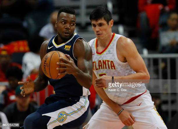 Paul Millsap of the Denver Nuggets drives against Ersan Ilyasova of the Atlanta Hawks at Philips Arena on October 27 2017 in Atlanta Georgia NOTE TO...