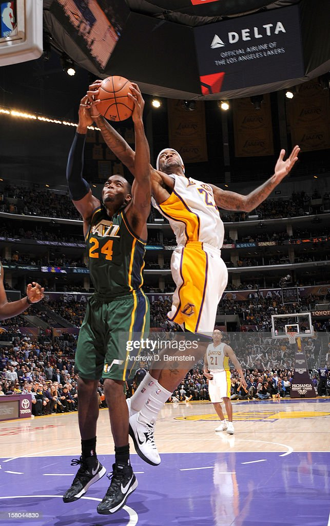 Paul Millsap #24 of the Utah Jazz and Jordan Hill #27 of the Los Angeles Lakers reach for a rebound at Staples Center on December 9, 2012 in Los Angeles, California.