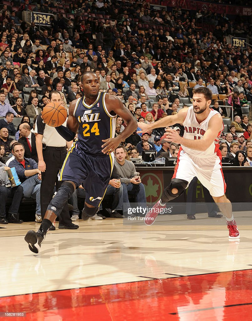 Paul Millsap #24 of the Utah Jazz drives against Linas Kleiza #11 of the Toronto Raptors during the game between the Toronto Raptors and the Utah Jazz on November 12, 2012 at the Air Canada Centre in Toronto, Ontario, Canada.