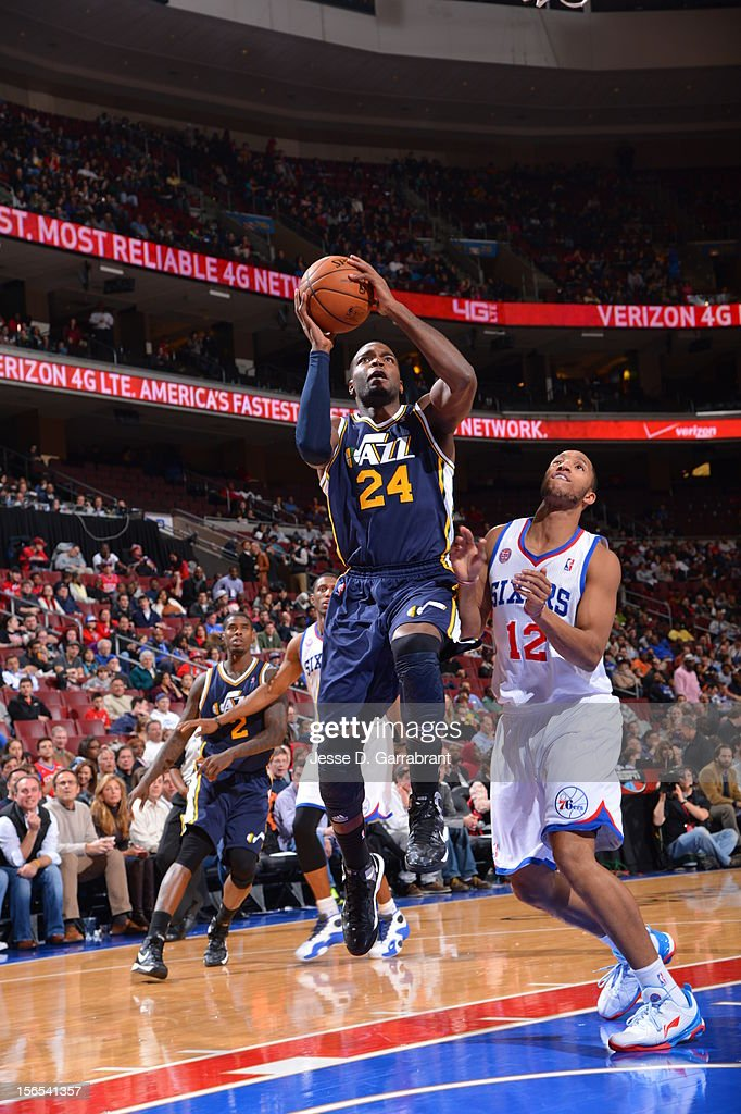 Paul Millsap #24 of the Utah Jazz drives to the basket against Evan Turner #12 of the Philadelphia 76ers at the Wells Fargo Center on November 16, 2012 in Philadelphia, Pennsylvania.
