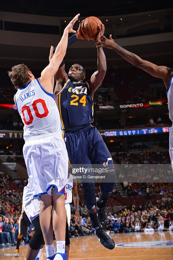 Paul Millsap #24 of the Utah Jazz drives to the basket against Spencer Hawes #00 of the Philadelphia 76ers at the Wells Fargo Center on November 16, 2012 in Philadelphia, Pennsylvania.