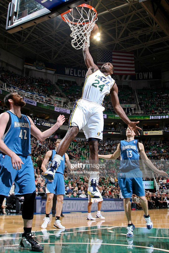 Paul Millsap #24 of the Utah Jazz dunks against Kevin Love #42 of the Minnesota Timberwolves at Energy Solutions Arena on January 2, 2013 in Salt Lake City, Utah.