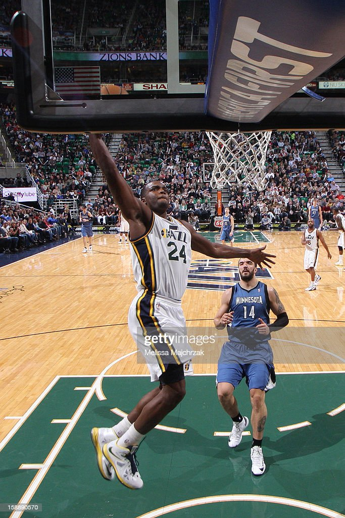 Paul Millsap #24 of the Utah Jazz dunks on a fast break ahead of Nikola Pekovic #14 of the Minnesota Timberwolves at Energy Solutions Arena on January 2, 2013 in Salt Lake City, Utah.
