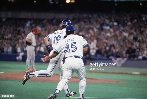 Paul Molitor of the Toronto Blue Jays is greeted by third base coach Nick Leyva as he runs the bases after hitting a home run off of pitcher Mitch...