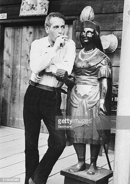 Paul Newman who stars in the movie Hombre took time out from acting chores on location to smoke a Panatela in company with a cigar store Indian in...