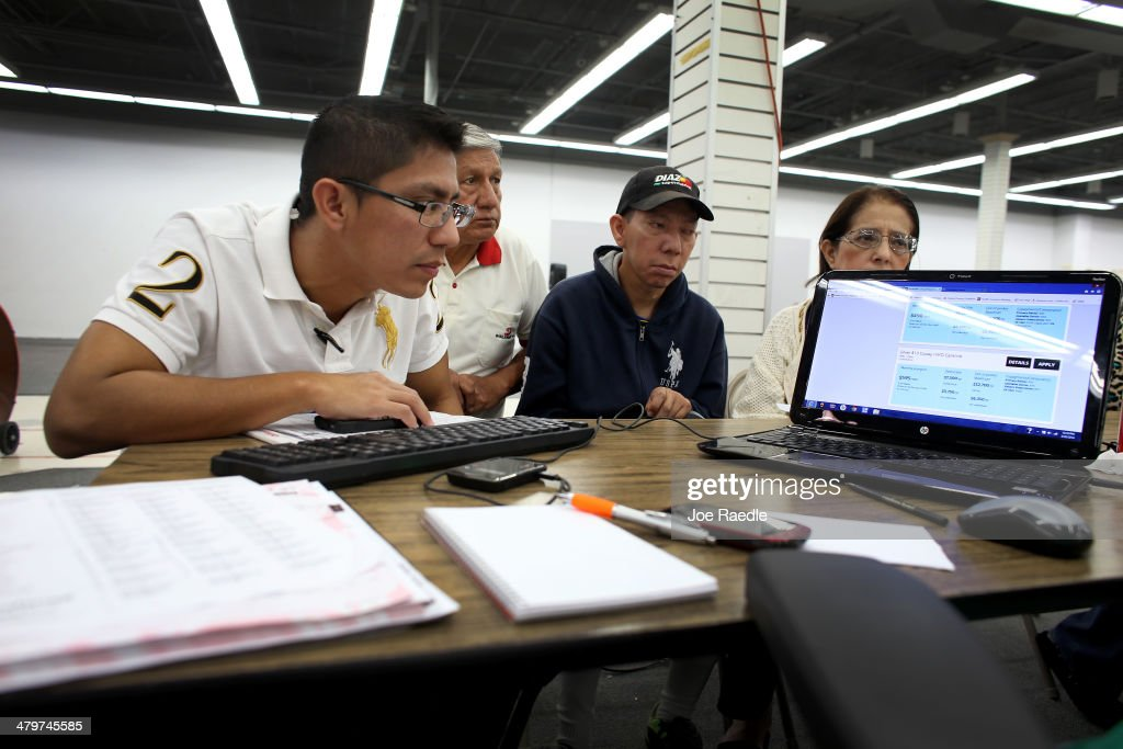Paul Paucar (L-R), Homero Paucar, Giovanny Paucar and Ivonne Cucalon check the price plans for health insurance under the Affordable Care Act as they sit with an insurance agent from Sunshine Life and Health Advisors at a store setup in the Mall of Americas on March 20, 2014 in Miami, Florida. The owner of Sunshine Life and Health Advisors, Odalys Arevalo, said she has seen a surge in people, some waiting up to 3 hours or more in line, trying to sign up for the Affordable Care Act before the open enrollment period for individual insurance ends on March 31.