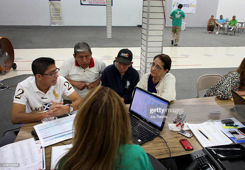 Paul Paucar (L-R), Homero Paucar, Giovanny Paucar and Ivonne Cucalon sit with, Jessica Adames, an insurance agent from Sunshine Life and Health Advisors as they try to purchase health insurance under the Affordable Care Act at a store setup in the Mall of Americas on March 20, 2014 in Miami, Florida. The owner of Sunshine Life and Health Advisors, Odalys Arevalo, said she has seen a surge in people, some waiting up to 3 hours or more in line, trying to sign up for the Affordable Care Act before the open enrollment period for individual insurance ends on March 31.