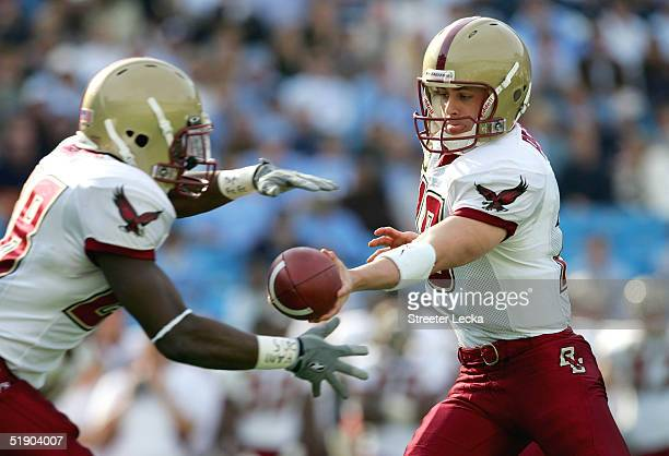 Paul Peterson of the Boston College Golden Eagles hands off the ball to teammate AJ Brooks in their game against the University of North Carolina Tar...