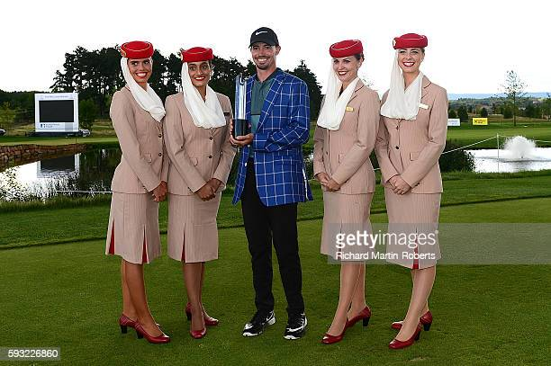 Paul Peterson of the United States poses with the trophy and the Emirates girls following his victory during the final round of the DD REAL Czech...