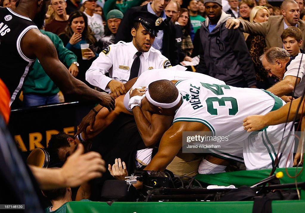Paul Pierce #34 and Rajon Rondo #9 of the Boston Celtics fight with Kris Humphries #43 of the Brooklyn Nets while security and referees attempt to break it up behind the basket after Humphries fouled Kevin Garnett #5 of the Boston Celtics during the game on November 28, 2012 at TD Garden in Boston, Massachusetts. Kris Humphries and Rajon Rondo would be immediately ejected from the game.