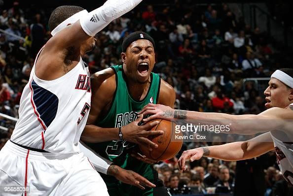 Paul Pierce of the Boston Celtics drives against Josh Smith and Mike Bibby of the Atlanta Hawks at Philips Arena on January 8 2010 in Atlanta Georgia...