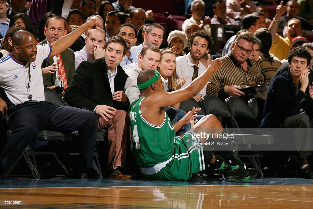 Paul Pierce #34 of the Boston Celtics falls on actor Jimmy Fallon (L), English footballer Wayne Rooney (M) and his girlfriend Coleen McLoughlin (R) during the New York Knicks game against the Boston Celtics at Madison Square Garden on December 11, 2006 in New York City. The Celtics won 97-90.