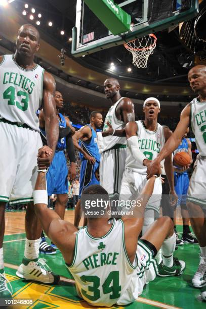 Paul Pierce of the Boston Celtics is helped up by Kendrick Perkins Kevin Garnett Rajon Rondo and Ray Allen during action against the Orlando Magic in...