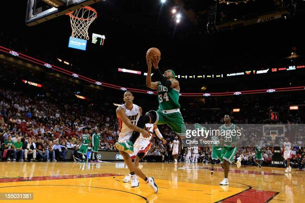 Paul Pierce of the Boston Celtics lays the ball up past Shane Battier of the Miami Heat at American Airlines Arena on October 30 2012 in Miami...