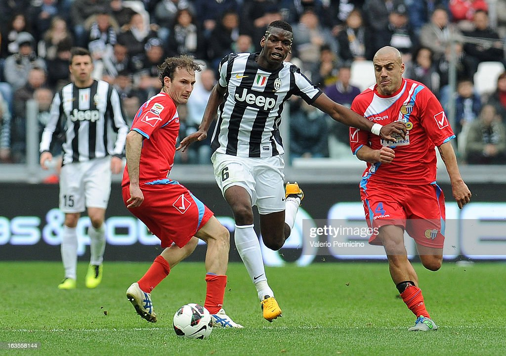 Paul Pogba (C) of FC Juventus is challenged by Sergio Bernardo Almiron (R) of Calcio Catania during the Serie A match between FC Juventus and Calcio Catania at Juventus Arena on March 10, 2013 in Turin, Italy.