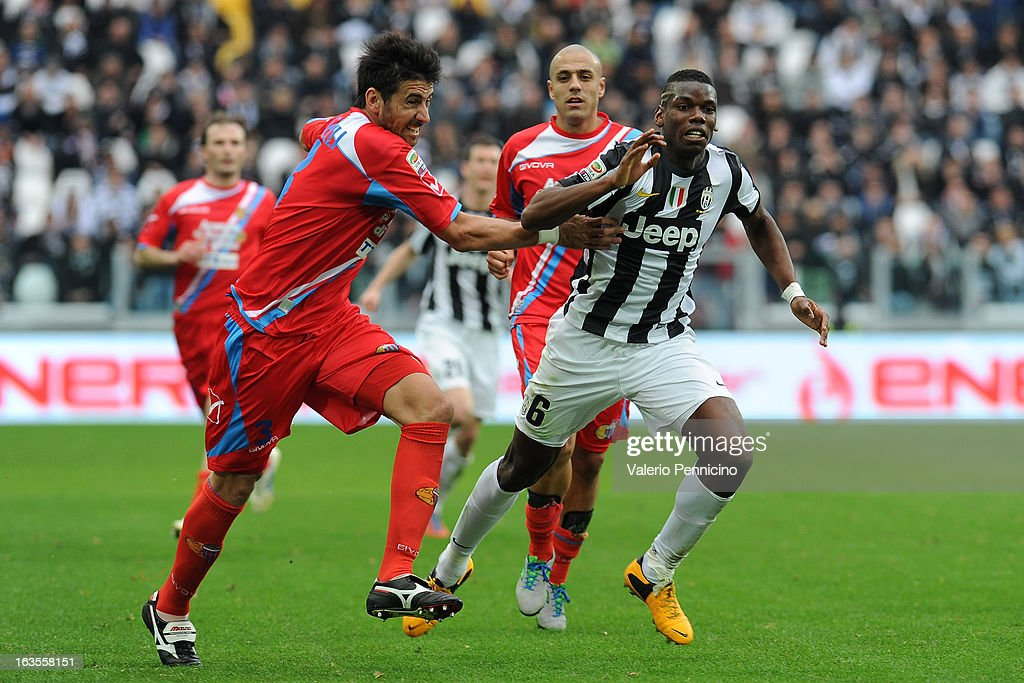 Paul Pogba (R) of FC Juventus is pulled by his shirt by Nicolas Federico Spolli of Calcio Catania during the Serie A match between FC Juventus and Calcio Catania at Juventus Arena on March 10, 2013 in Turin, Italy.