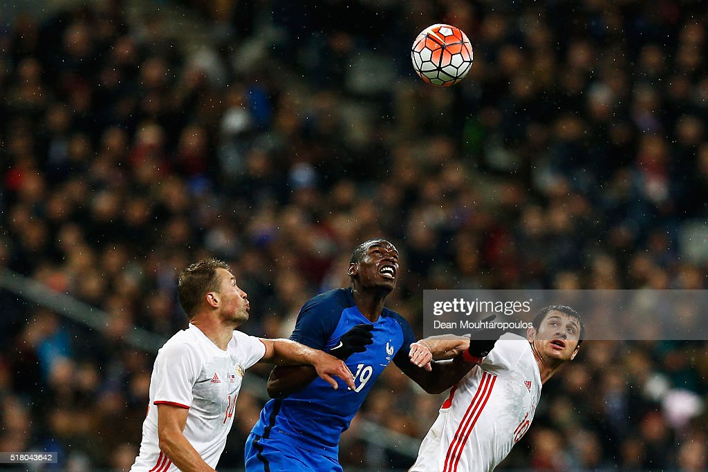 Paul Pogba of France battles for the ball with Vasily Berezutski (L) and Alan Dzagoev (R) of Russia during the International Friendly match between France and Russia held at Stade de France on March 29, 2016 in Paris, France.