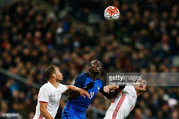 Paul Pogba of France battles for the ball with Vasily Berezutski and Alan Dzagoev of Russia during the International Friendly match between France...